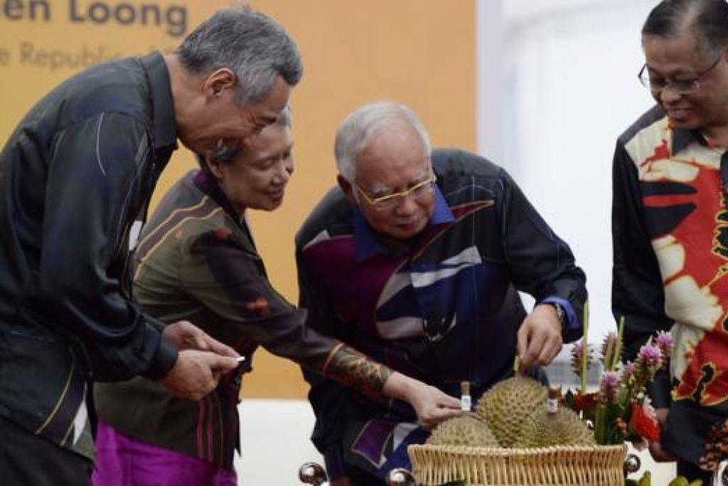 MEM'BUAH'KAN HASIL: (Dari kiri) PM Lee dan isteri, Cik Ho Ching, melihat durian 'Musang King' yang ditunjukkan oleh Datuk Seri Najib di pelancaran Agrobazaar semalam, dengan diperhatikan Menteri Pertanian dan Industri Asas Tani Malaysia, Datuk Sri Ismail Sabri Yaakob (kanan). - Foto THE STRAITS TIMES