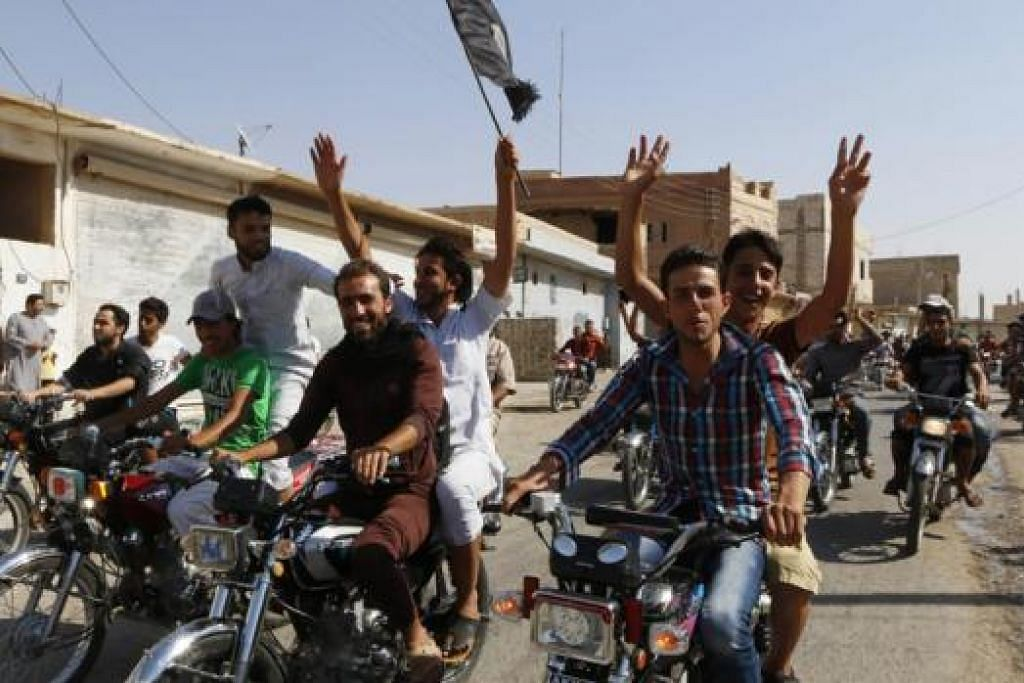 MERAIKAN KEMENANGAN: Penduduk di Tabqa yang mengibarkan bendera gembira selepas pangkalan udara Tabqa jatuh kepada militan IS. - Foto REUTERS