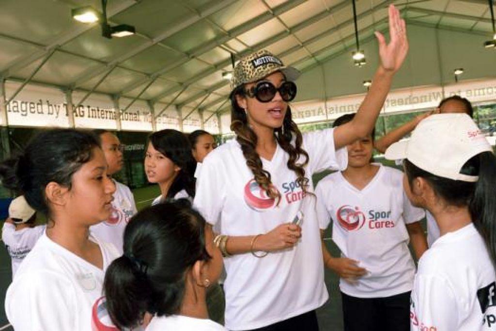 MESRA DENGAN SI CILIK: Bintang Glee, Erinn Westbrook (bertopi dan berkaca mata hitam), yang berkelulusan Universiti Harvard, senang mengembara ke Singapura untuk menyuntik keyakinan diri kepada kanak-kanak dan belia yang memerlukan dorongan.