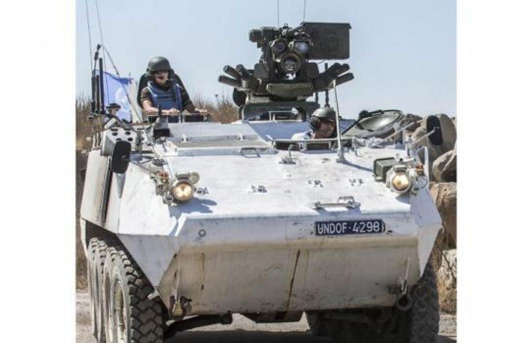 KAWASAN BAHAYA: Pasukan pengaman dari Ireland memantau keadaan di Bukit Golan sebelum ia melintas sempadan memasuki wilayah yang dikawal Syria, kelmarin. - Foto AFP