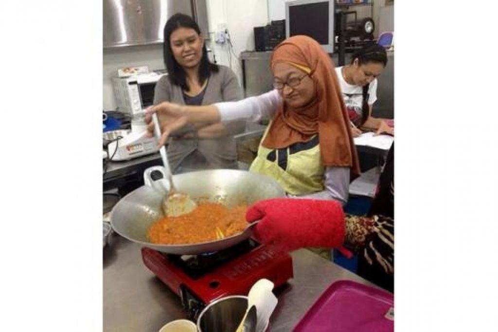 GIGIH BERDIKARI: Walaupun sukar, Cik Suhana Suhaimi bersemangat menumis rencah lauk ayam masak merah secara sendiri sambil diperhatikan seorang rakan sekelasnya.