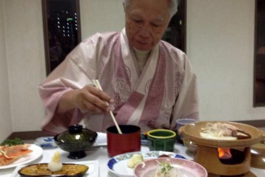 CUBA-CUBA: Suami penulis, Johar Anuar, mencuba makanan tradisi Jepun lengkap pakaian Jepun juga. - Foto-foto ihsan RAHIMAH MOHAMAD
