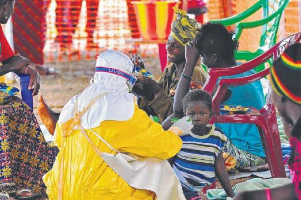 HULUR BANTUAN: Seorang pekerja perubatan menyuapkan makanan kepada seorang anak kecil yang dijangkiti virus Ebola di Kailahun.- Foto AFP