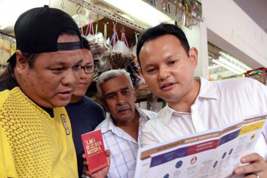 PEKEDAI TURUT SOKONG: Encik Zaqy menerangkan kepada EnciK Mohd Azmi tentang acara-acara Bulan Bahasa yang akan dilancarkan Sabtu ini sementara diperhatikan beberapa pekedai lain. - Foto ZAINAL YAHYA