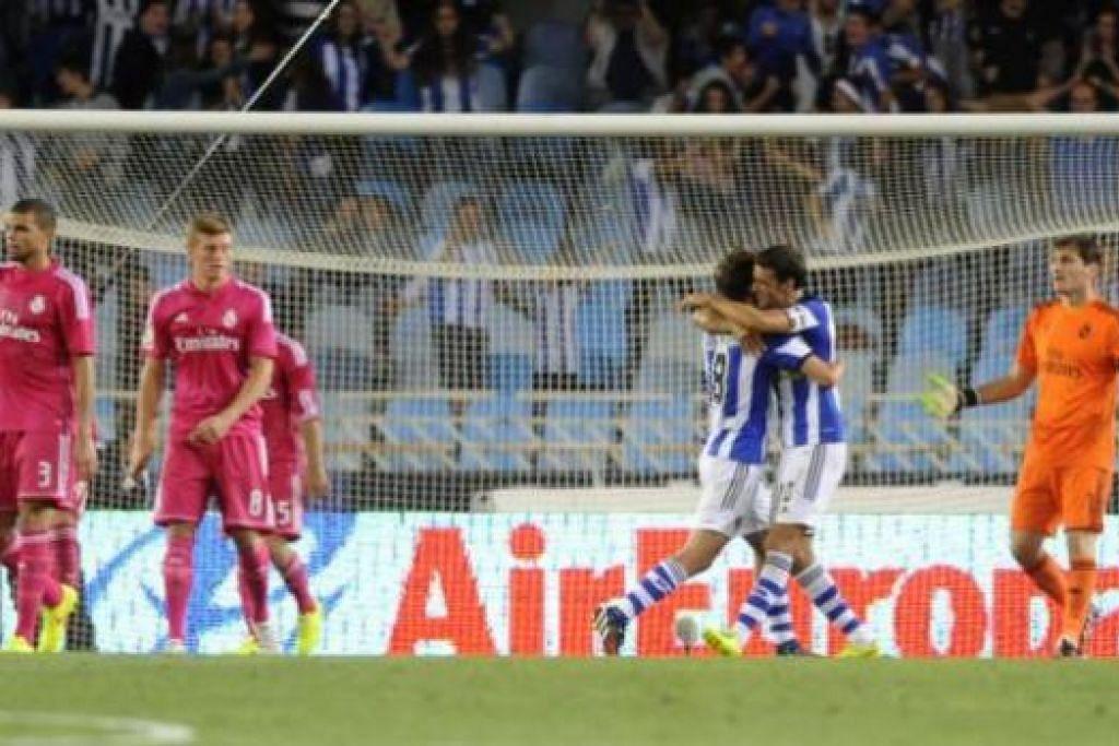 DUKA DAN GEMBIRA: Esteban Granero (tiga dari kanan) memeluk erat rakan sepasukan Xabi Prieto selepas menjaringkan gol keempat Real Sociedad bagi membolehkan mereka mengejutkan Real Madrid di Stadium Anoeta di San Sebastian kelmarin. - Foto AFP