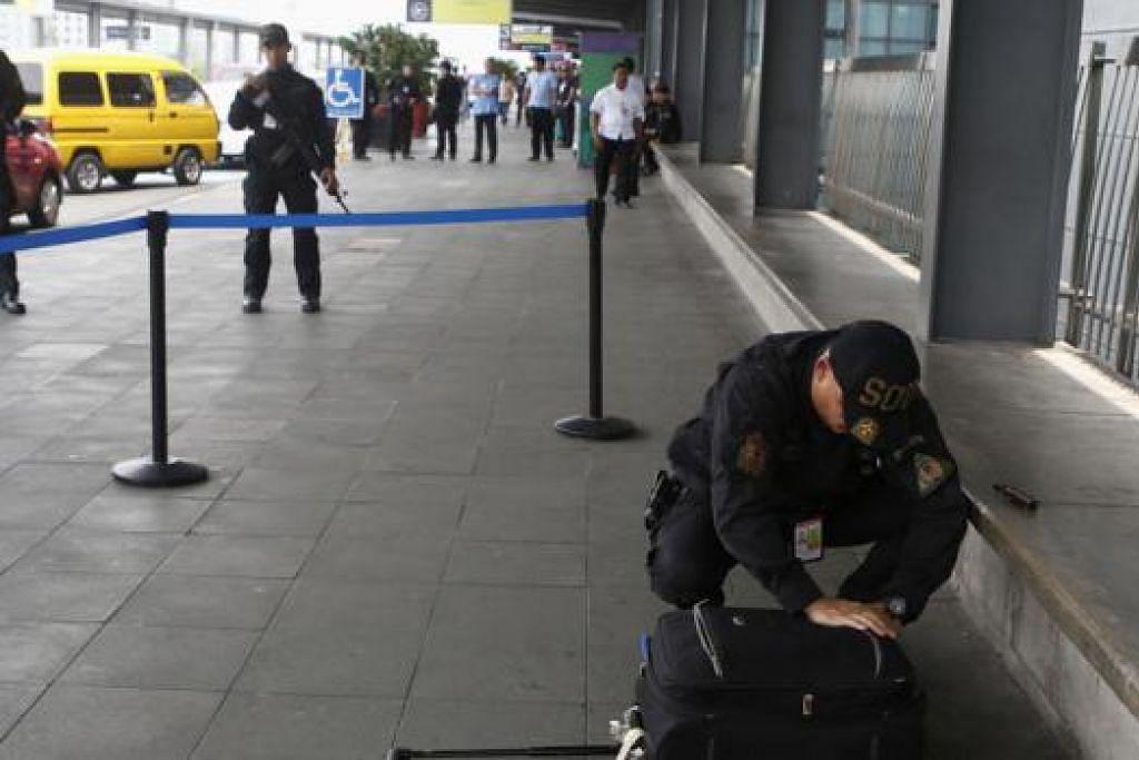 BERJAGA-JAGA: Seorang anggota polis memeriksa beg yang dijumpai ditinggalkan di luar terminal tiga Lapangan Terbang Antarabangsa Ninoy Aquino, Manila, selepas bom dijumpai dalam sebuah kenderaan di tempat meletak kereta terminal itu. - Foto REUTERS