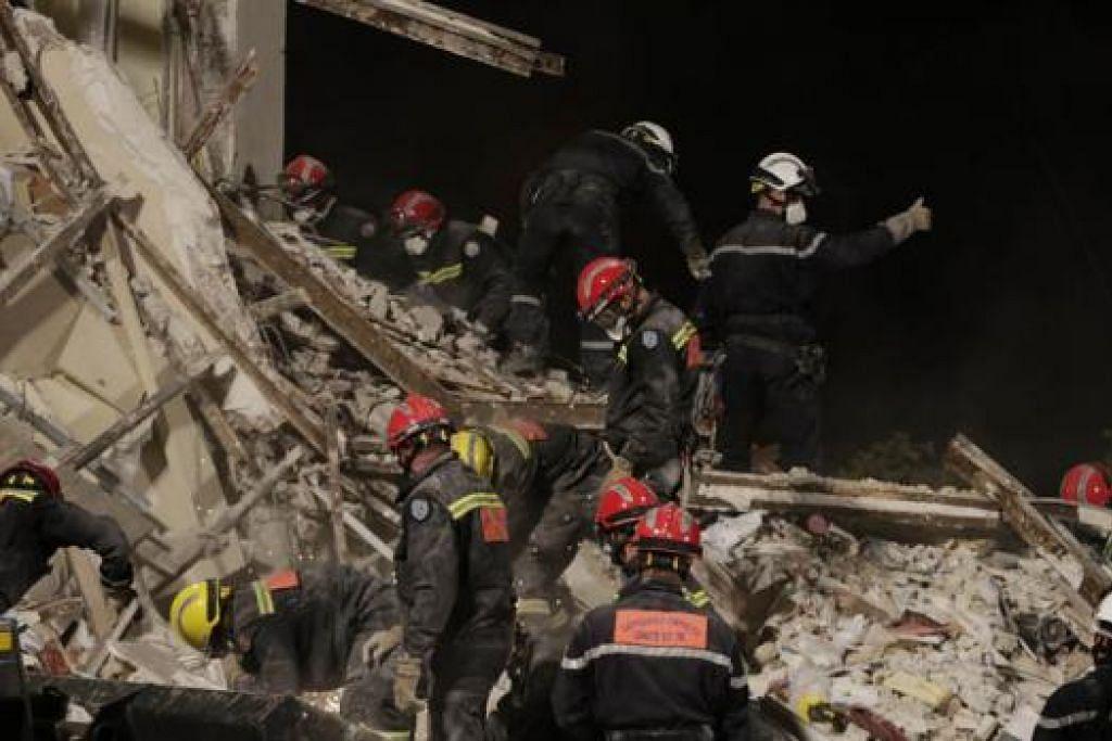 ADA YANG MASIH HILANG: Ahli bomba meneruskan usaha mencari mangsa di bawah puing apartmen yang runtuh di bandar Rosny-sous-Bois kelmarin. - Foto AFP