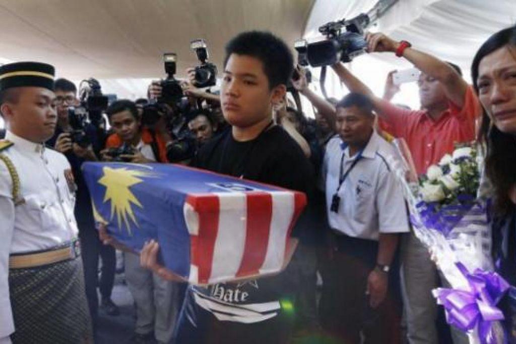 MENAHAN SEBAK: Melvic Choo, 13 tahun, membawa abu mendiang ayahnya, pembantu juruterbang MH17, mendiang Eugene Choo, sementara ibunya, Cik Ivy Loi, yang berdiri di sebelahnya berusaha mengawal perasaannya. Sembilan lagi jenazah mangsa nahas MH17 telah dibawa pulang semalam. - Foto REUTERS