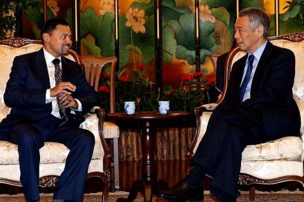 BERBUAL MESRA: Perdana Menteri, Encik Lee Hsien Loong (kanan), kelihatan sedang berbual mesra semasa menemui Putera Haji Al-Muhtadee, sebelum satu majlis makan tengah hari yang dihos Encik Lee, semalam. - Foto THE STRAITS TIMES