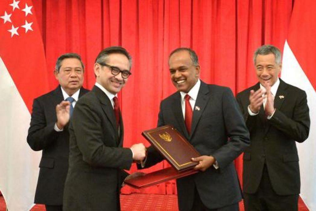 SAKSI PERJANJIAN: Presiden Yudhoyono (kiri) dan Encik Lee (kanan) turut menyaksikan menteri luar masing-masing, Encik Marty Natalegawa (dua dari kiri) dan Encik K Shanmugam, memeterai perjanjian penyempadanan laut antara Singapura dan Indonesia.