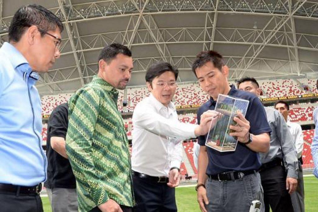 KUNJUNGAN TETAMU ISTIMEWA: Putera Haji Al-Muhtadee Billah (berbaju hijau) mendengar taklimat tentang Hab Sukan Singapura dan Stadium Negara semasa lawatan beliau ke sana. Antara lain, beliau ditemani Encik Lawrence Wong (tengah) dan Dr Mohamad Maliki (kiri). - Foto JOHARI RAHMAT