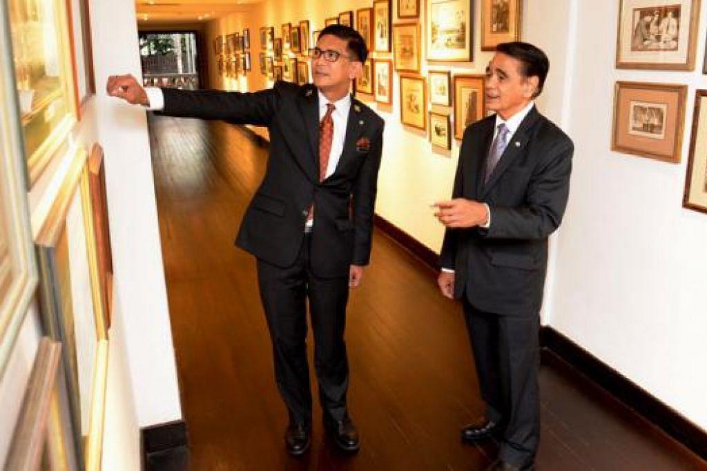 BELAJAR DARIPADA 'CIKGU': Encik Roslee Sukar (kiri) mendapat tunjuk ajar mentornya, Encik Leslie Danker, yang bertindak sebagai sejarawan tetap di Hotel Raffles. Di sini, mereka menyusuri jalan kenangan hotel legenda itu yang dibuka pada 1887 menerusi koleksi foto-foto lama, yang antara lain memaparkan gambar selebriti atau tokoh ternama yang pernah menginap di Hotel Raffles.