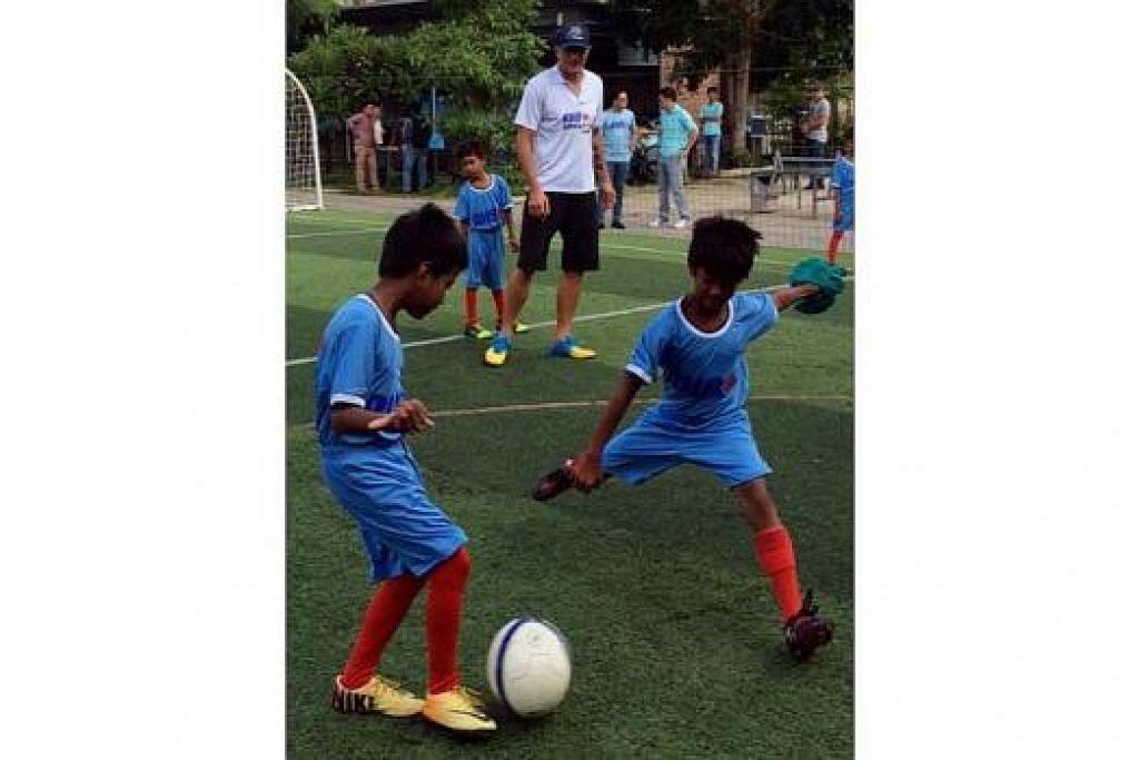 TIDAK LOKEK KONGSI ILMU: Aleksandar Duric (berkemeja-T putih) memberi tunjuk ajar kepada kanak-kanak kurang bernasib baik di Kemboja dalam satu klinik bola sepak yang diadakan di Phnom Penh petang kelmarin. - Foto PERSATUAN BOLA SEPAK SINGAPURA