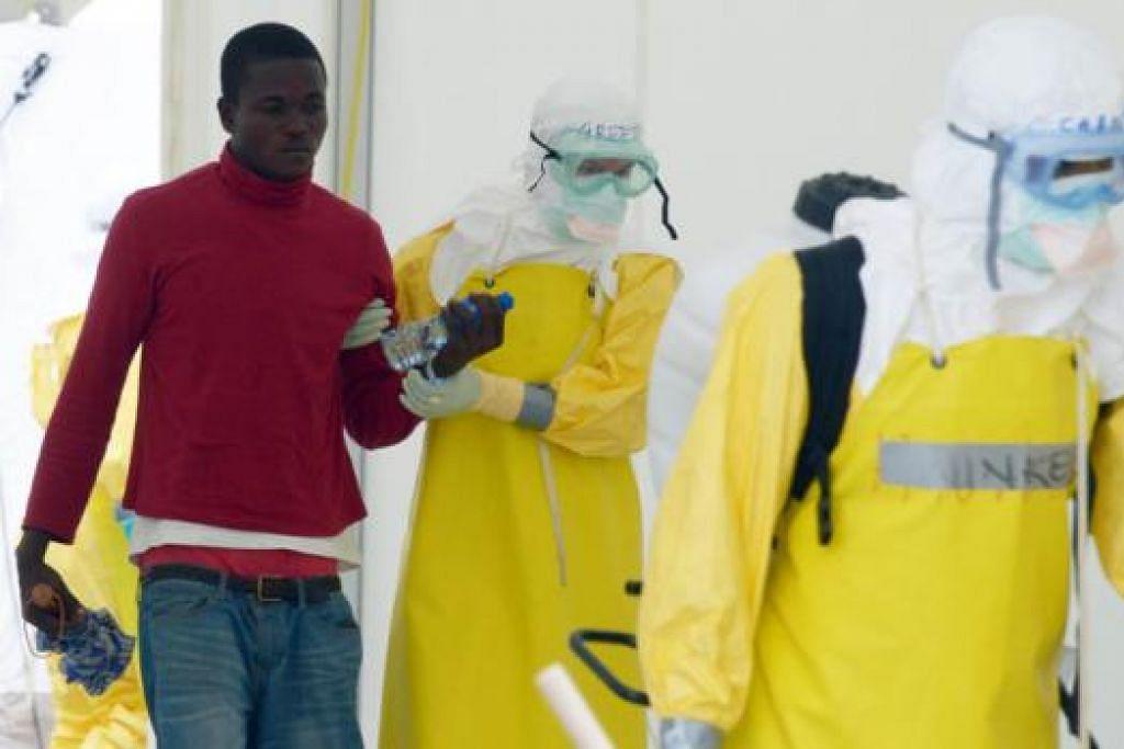 WABAK BELUM DAPAT DIKAWAL: Pekerja kesihatan yang mengenakan pakaian perlindungan tiba di sebuah hospital di Monrovia, Liberia, dengan seorang pesakit yang disyaki dijangkiti virus Ebola. - Foto AFP