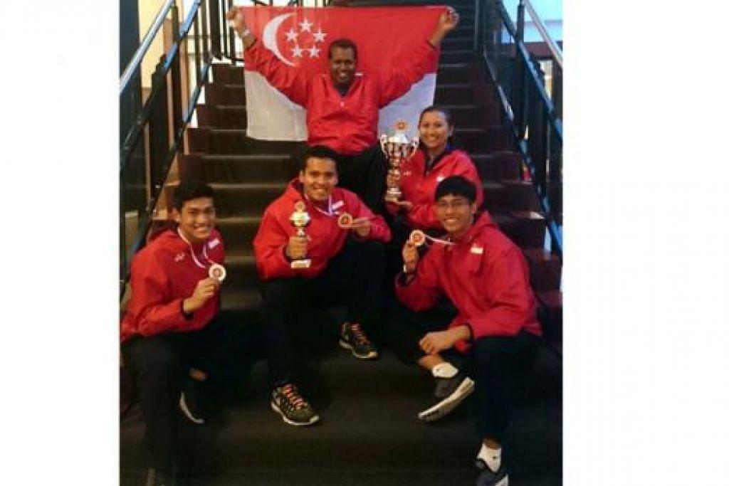 JUARA DENGAN PENGIRING: (Dari kiri) Muhammad Iqbal Abdul Rahman, Muhammad Shakir Juanda dan Muhammad Nur Alfian Juma'en menunjukkan pingat emas dan piala yang dimenangi dalam Kejohanan Pencak Silat Antarabangsa 2014 yang berlangsung di Roermond, Belanda, pada hujung minggu lalu. Turut mengiringi mereka ialah CEO Persisi, Sheik Alau'ddin Yacoob Marican (memegang bendera), dan seorang pegawai Persisi. - Foto PERSISI