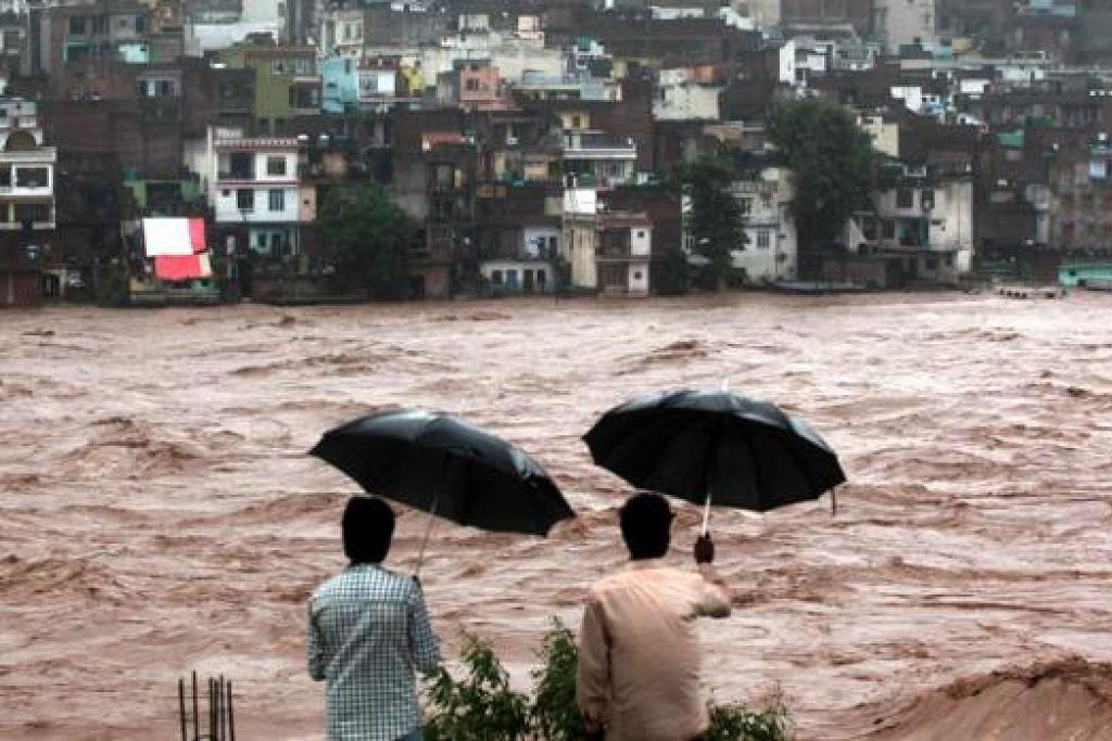 TERUS ANCAM: Penduduk melihat rumah yang diancam air dari Sungai Tawi di Jammu. Hujan yang berterusan dan banjir di utara India telah mengorbankan lebih 150 jiwa. - Foto AFP