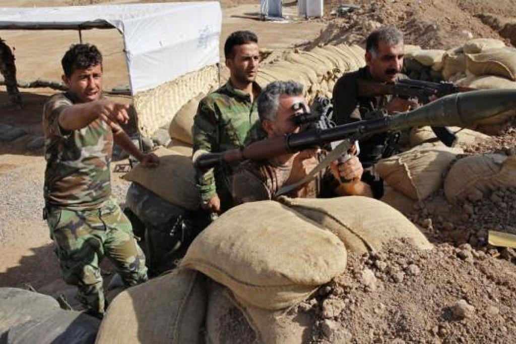 SIAP BERTEMPUR: Pejuang peshmerga Kurdi mengambil kedudukan sedang kereta kebal mereka membedil kedudukan militan IS di Mosul, Iraq. - Foto REUTERS