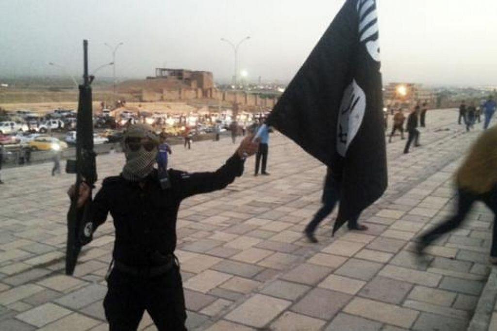 DAKWAAN PALSU: Seorang militan ISIS mengangkat senjata sambil mengibar panji-panji kumpulan di Mosul, utara Iraq, Jun lalu. Dengan menggunakan kalimah syahadah dan nama Nabi Muhammad saw pada panji-panjinya, militan ISIS mendakwa kononnya mereka memperjuangkan Islam. - Foto REUTERS