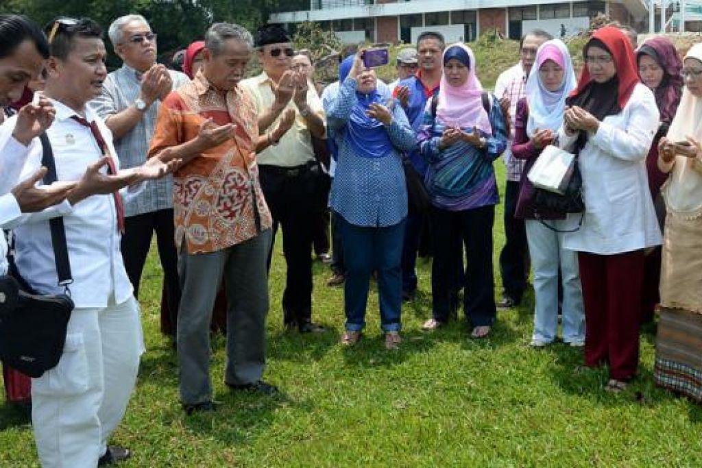 KUNJUNGAN TERAKHIR: Bekas pelajar Sekolah Menengah Sang Nila Utama, termasuk Encik Yatiman Yusof (berbaju batik warna jingga), membaca doa di padang bola sepak di belakang sekolah semasa kunjungan mereka ke sana Isnin lalu.