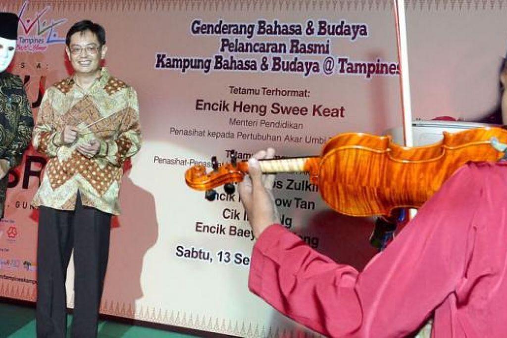 RASMIKAN ACARA: Encik Heng (dua dari kiri) menjadi konduktor kepada orkestra Sri Temasek, menandakan pelancaran acara Bulan Bahasa di Tampines. - Foto-foto TAUFIK A. KADER