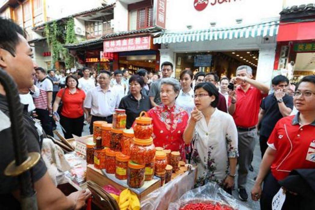 TINJAU TARIKAN: Encik Lee (berkemeja-T merah memegang kamera) memetik foto semasa di Yangshuo West Street sedang isterinya, Cik Ho Ching (depan, tiga dari kanan), meninjau-ninjau barangan tempatan yang dijual di sana. - Foto MCI