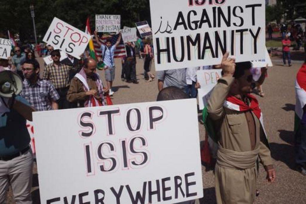 TENTANG IS: Para penunjuk perasaan berdekatan Rumah Putih semalam menentang kekejaman IS di Syria dan Iraq yang dikatakan melakukan pembunuhan beramai-ramai, yang terbaru di kawasan kampung Kocho di utara Iraq. - Foto AFP