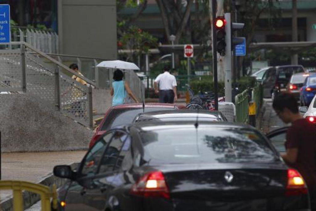 MELETAK KERETA SEMBARANGAN: Sesetengah pemandu masih meletakkan kenderaan mereka secara sembarangan walaupun LTA telah memasang papan tanda mengingatkan pemandu tentang CCTV yang sudah dipasang. - Foto fail