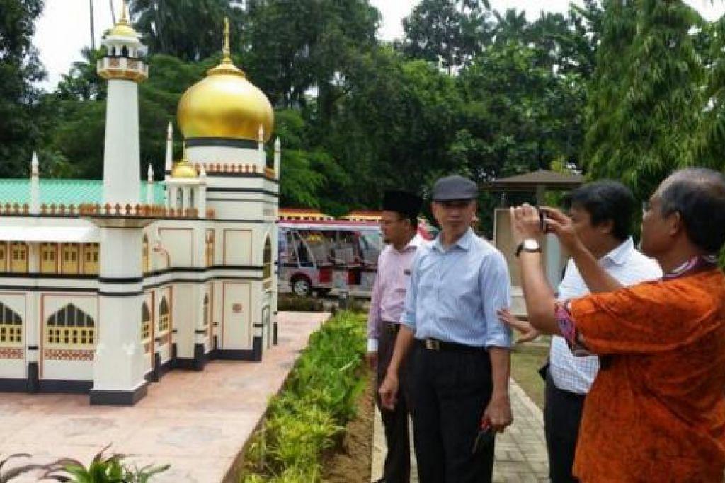 LAWATAN: Encik Masagos (paling kanan) merakamkan foto model Masjid Sultan yang dipamerkan di Taman Tamadun Islam di Terengganu semasa mengadakan kunjungan ke negeri Malaysia itu. - Foto CHAIRUL FAHMY HUSSAINI