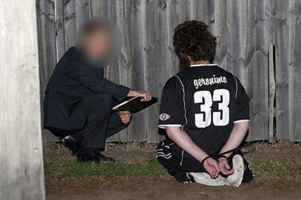 DISOAL SIASAT: Seorang pegawai polis Australia menyoal siasat seorang suspek di barat Sydney. - Foto REUTERS