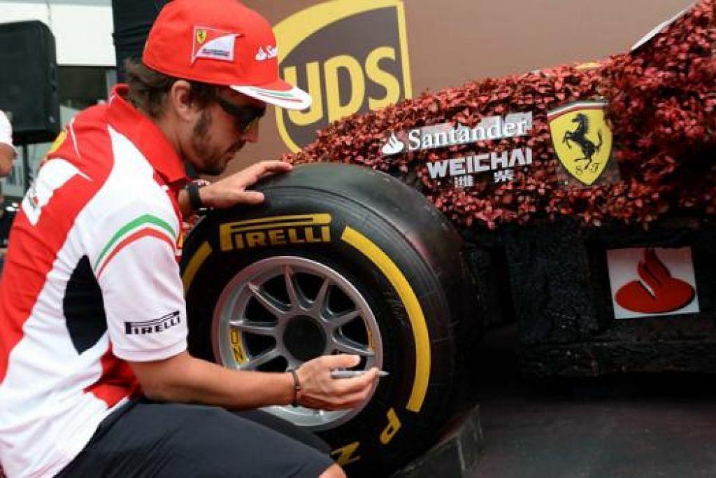 TINGGALKAN KENANGAN: Pemandu Ferrari, Fernando Alonso, sedang menandatangani di tayar sebuah kereta replika Formula 1. – Foto ZAINAL YAHYA