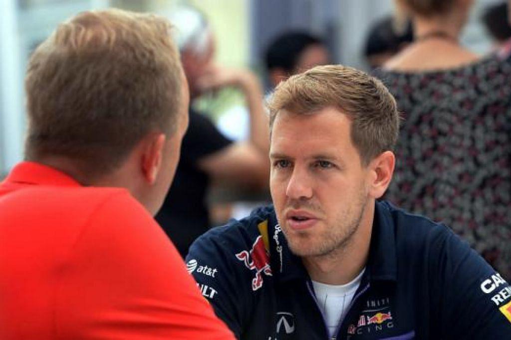 SIBUK WAWANCARA: Pemandu Red Bull, Sebastian Vettel, sedang diwawancara wartawan di kawasan litar Grand Prix Singapura di Marina Bay. – Foto ZAINAL YAHYA