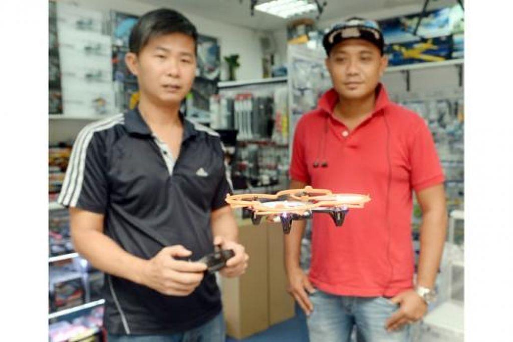UNTUK PENGGIAT BARU: Pemilik kedai Hobby Square, Encik Eddie Chan (kiri), bersama pelanggannya, Encik Nor Azman, menyaksikan dron saiz kecil model Hubsan X4 yang popular di kalangan mereka yang baru kepada dron. - Foto TAUFIK A. KADER