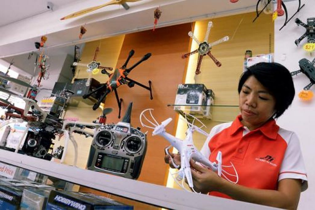 MACAM-MACAM ADA: Pengurus penjualan Jet Hobby RC Model, Cik Jariah Tohaiee, menunjukkan antara model dron yang terdapat di kedainya dalam kawasan Ubi. - Foto TUKIMAN WARJI