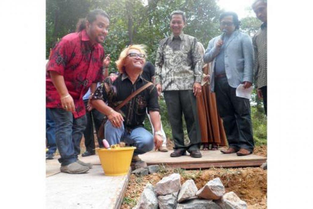 MULA PECAH TANAH: Mohamed Noor (baju merah) dan abangnya Mohamed Rasid meletakkan batu sebagai tanda majlis pembetonan resort mereka di Batam. - Foto FARID HAMZAH