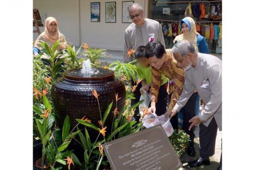 TANDA ULANG TAHUN: Encik Chan (berbaju batik) bersama presiden Persatuan Muhammadiyah, Ustaz Shaik Hussain Shaik Yaacob (kanan), memasukkan 25 ikan ke dalam kolam sebagai tanda usia RKM 25 tahun. - Foto TAUFIK A. KADER