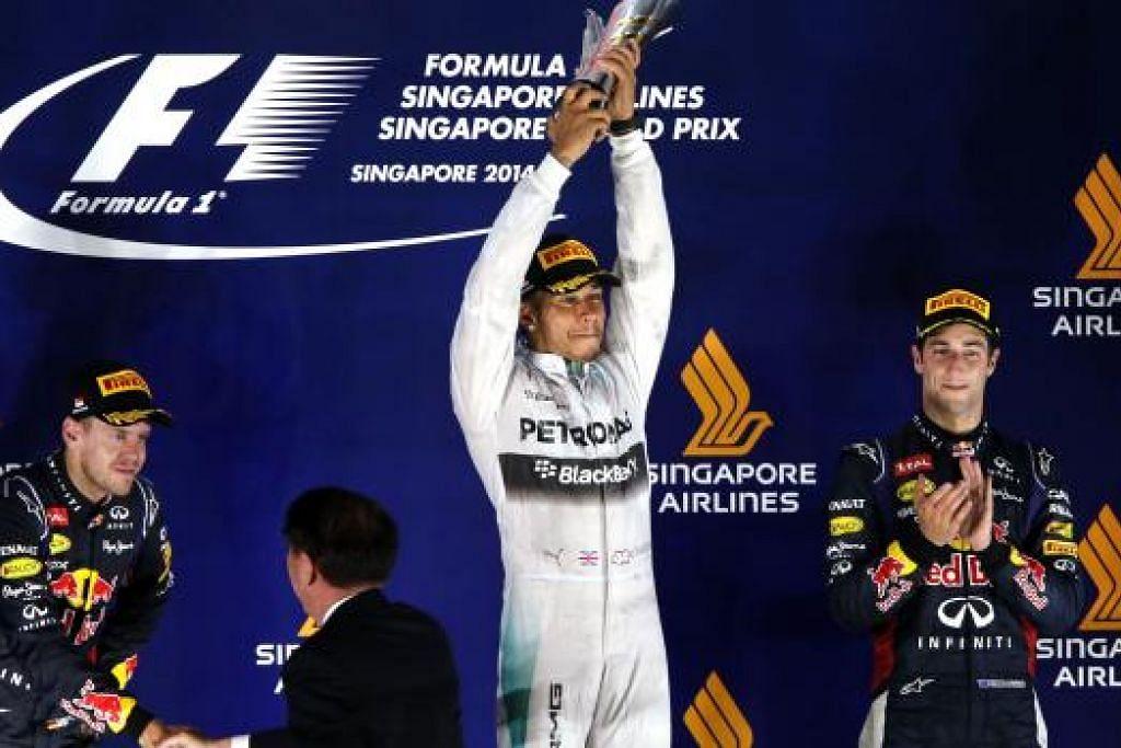 JUARA LAGI: Lewis Hamilton (tengah) ialah juara GP Singapura - kali kedua beliau memenangi perlumbaan di litar Marina Bay sejak 2009. Naib juara ialah pemandu Red Bull Renault Sebastian Vettel (kiri) dan Daniel Ricciardo.