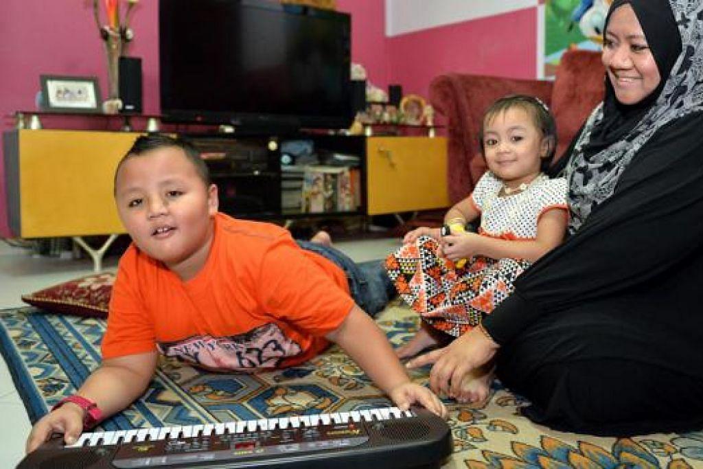SUKA MENEROKA: Cik Nurashika terpaksa memasang sistem penggera di pintu rumah bagi memastikan anak sulungnya yang mengalami autisme, Aqil Naufal Ataman, tidak dapat meninggalkan rumah tanpa disedari. Di pangkuan adalah anak keduanya, Nur Elveena Ataman, tiga tahun, yang normal.