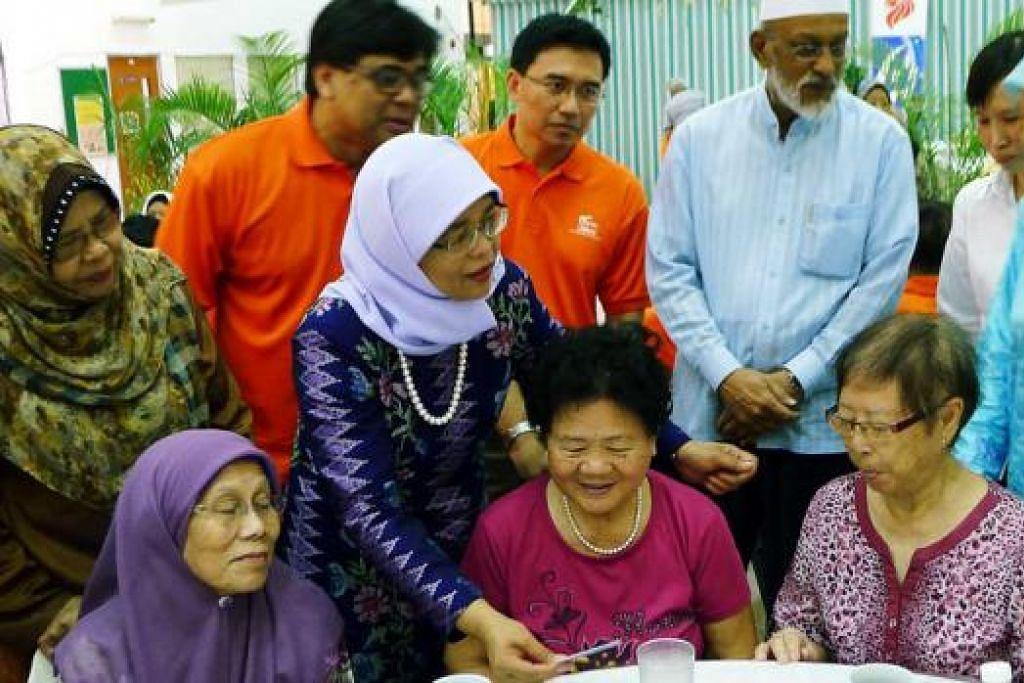 MANFAATKAN KAD: Cik Halimah (berdiri, dua dari kiri) beramah-tamah dengan warga tua sambil menunjukkan kepada mereka kad perintis yang boleh mereka manfaatkan. - Foto-foto KHALID BABA