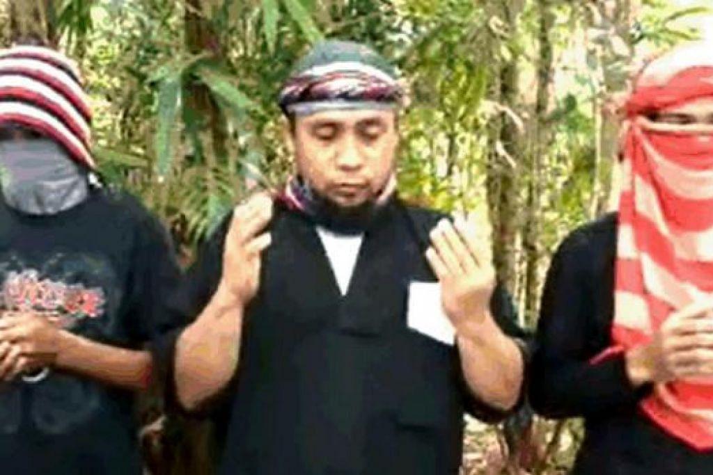 IKRAR TAAT SETIA: Pemimpin Abu Sayyaf, Isnilon Hapilon (tengah), mengikrarkan taat setia kepada militan IS dalam video yang dimuat naik ke YouTube. - Foto YOUTUBE