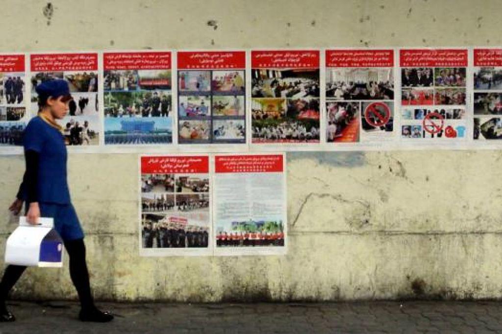 ANTI- KEGANASAN: Poster-poster antikeganasan ditampal di sepanjang jalan raya di Urumqi, Xinjiang. Dalam keganasan terbaru, sekurang- kurangnya dua orang terbunuh dan ramai lagi cedera dalam beberapa letupan di barat Xinjiang. - Foto AFP