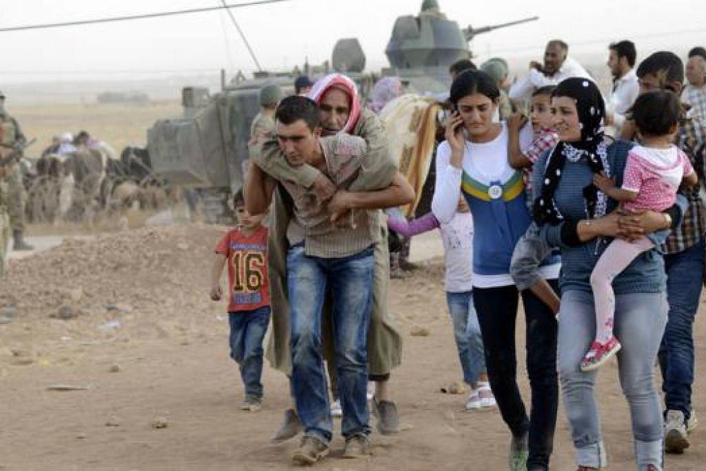 MENYELAMATKAN DIRI: Kaum Kurdi dari Syria melintasi sempadan dan memasuki Turkey bagi menyelamatkan diri daripada militan IS yang melancarkan serangan ke atas perkampungan mereka. - Foto REUTERS