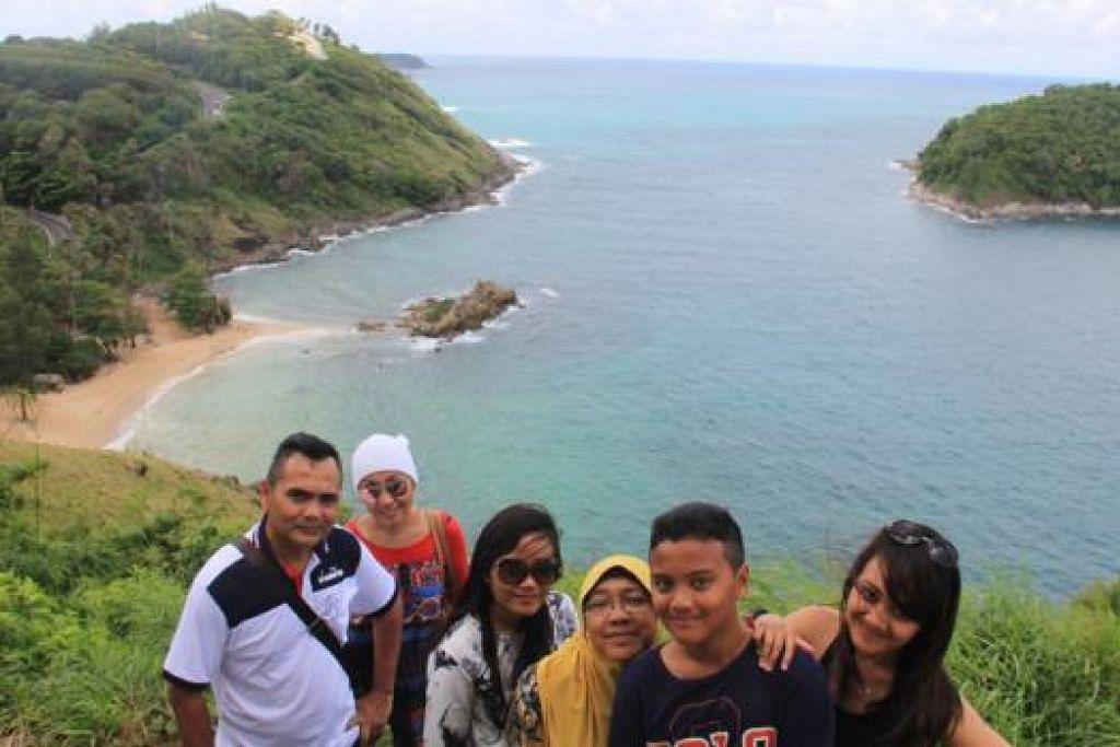 SAUJANA MATA MEMANDANG: Perkembangan Phuket selepas tsunami menarik perhatian penulis (kiri) yang sempat bergambar bersama keluarga di atas sebuah bukit di pulau itu. - Foto-foto NAZRY MOKHTAR