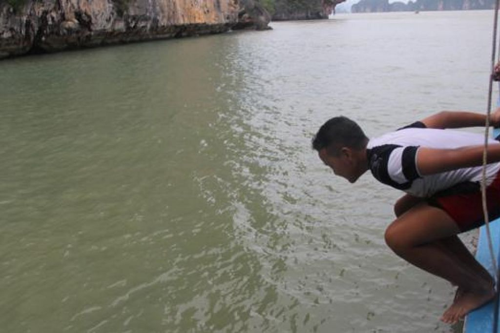 SERONOK BERENANG: Anak penulis melompat dari bot semasa kegiatan berenang dan snorkeling di Lautan Andaman.