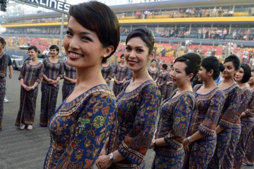 WAJAH BARU: Barisan gadis 'Singapore Girls' muncul di petak permulaan di Grand Prix Singapura buat pertama kali menyusuli tajaan buat julung-julung kali Singapore Airlines. - Foto AFP