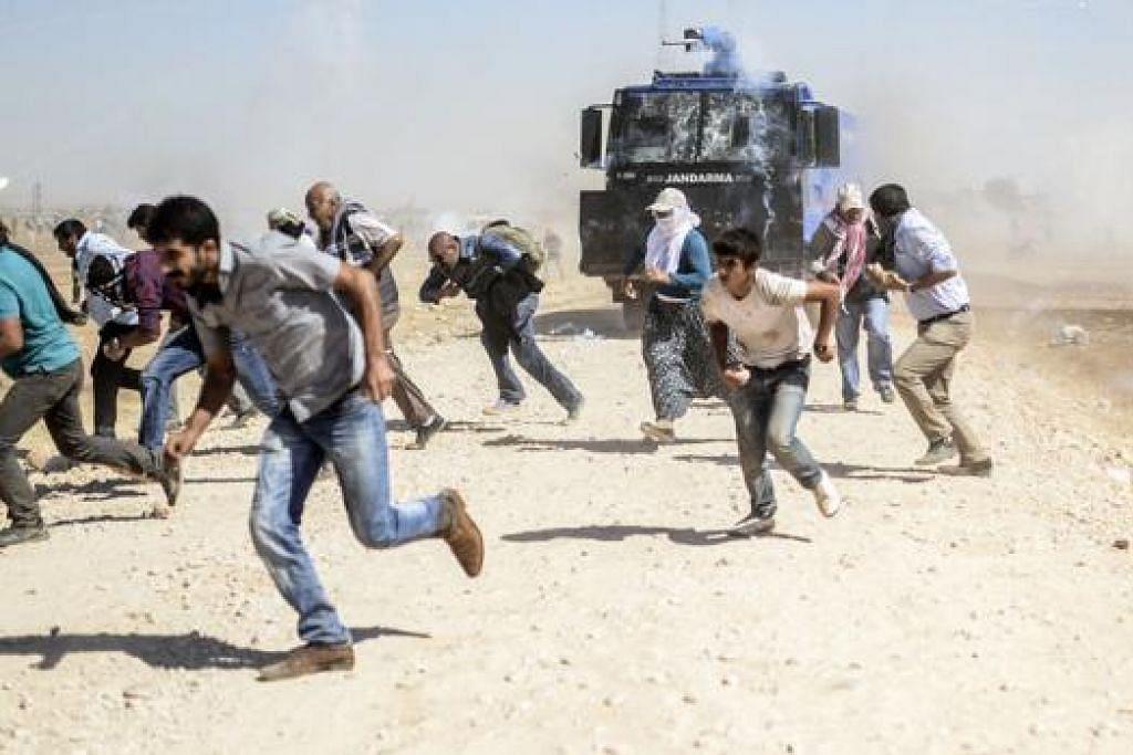 BERTEMPUR DI SEMPADAN: Pelarian Kurdi dekat sempadan Syria bertempur dengan askar Turkey selepas pihak berkuasa Turkey menutup kawasan sempadan selepas 130,000 pelarian menyeberang ke negara itu sejak beberapa hari lalu. - Foto AFP