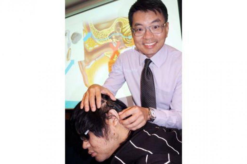 BANYAK MEMBANTU: Dr Yuen Heng Wai menunjukkan alat Bonebridge yang dipasang di bahagian kepala dekat dengan telinga Encik Ng Wei Xuan, pesakit hilang pendengaran sebelah telinga pertama menjalani pemindahan Bonebridge. - Foto JOHARI RAHMAT
