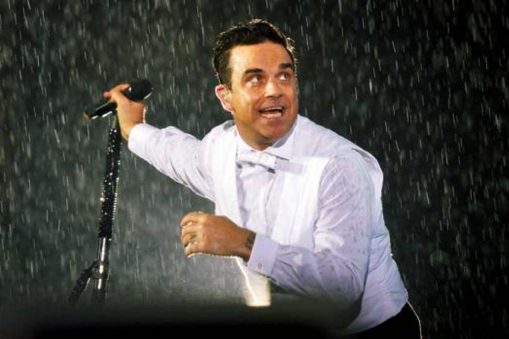 TETAP MENYANYI BIAR HUJAN: Penyanyi terkenal Britain, Robbie Williams, seronok menyanyi dan menghiburkan hadirin dalam hujan sempena acara hiburan Formula Satu Grand Prix Singapura Singapore Airlines 2014. - Foto KHALID BABA
