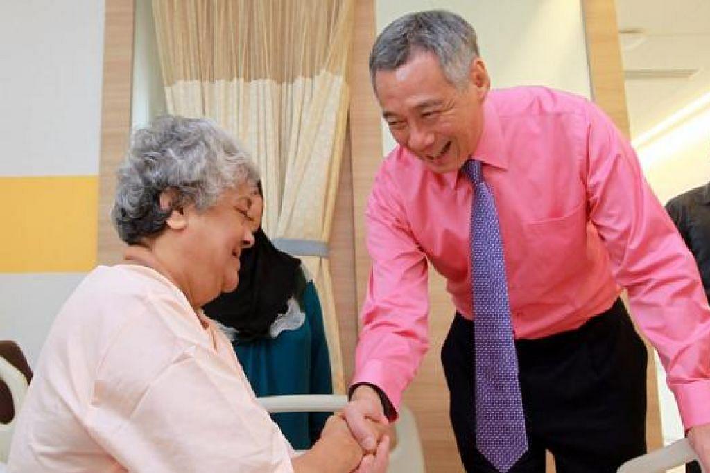 BERTANYA KHABAR: PM Lee menziarahi Cik Jenet Kani Mohd Ibrahim dan beberapa pesakit lain di Unit Inap Sementara (SSU) di bangunan baru Pusat Jantung Nasional Singapura (NHCS) yang dibuka secara rasmi, semalam. - Foto ZAOBAO