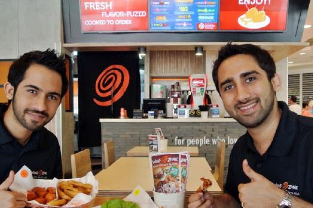 PENJUALAN MELONJAK: Encik Johnny Mayani (kanan) dan adiknya, Encik Mohit Mayani, menyaksikan penjualan meningkat 20 peratus selepas mendapat sijil halal bagi restoran Wing Zone di Century Square. - Foto JOHARI RAHMAT