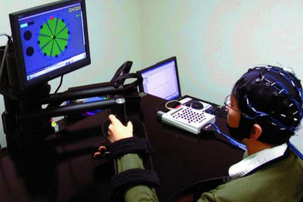 BANTU PESAKIT STROK: Teknologi baru yang dibangunkan A*Star membolehkan pesakit strok menjalani pemulihan menggunakan mesin robotik yang menggerakkan tangan pesakit, diaktifkan oleh isyarat elektrik yang dikesan alat yang dipakai di kepala. - Foto A*STAR